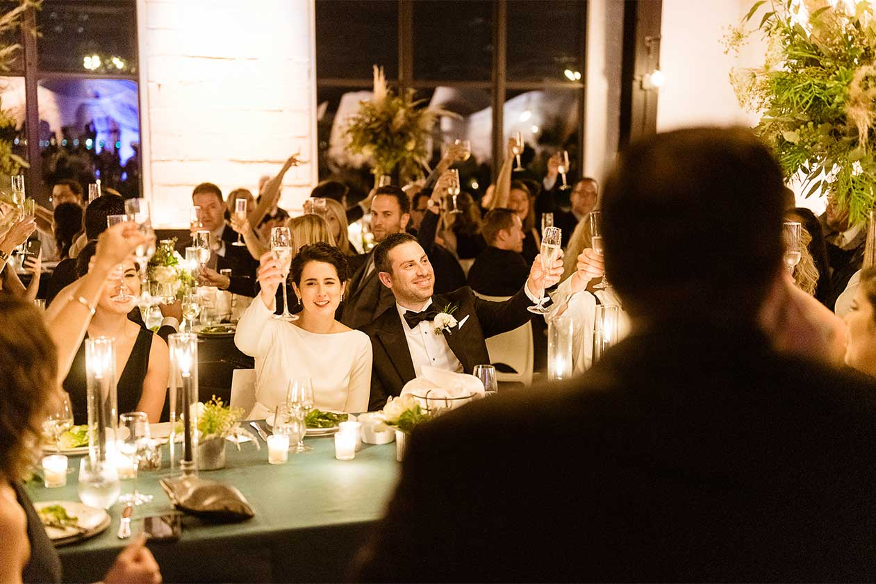 Best man wedding toast with both couple and crowd cheering and raising their glasses
