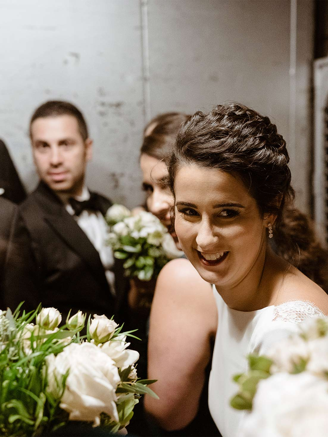 Bride smiles as bridal party rides in an industrial service freight to enter the westchester wedding venue
