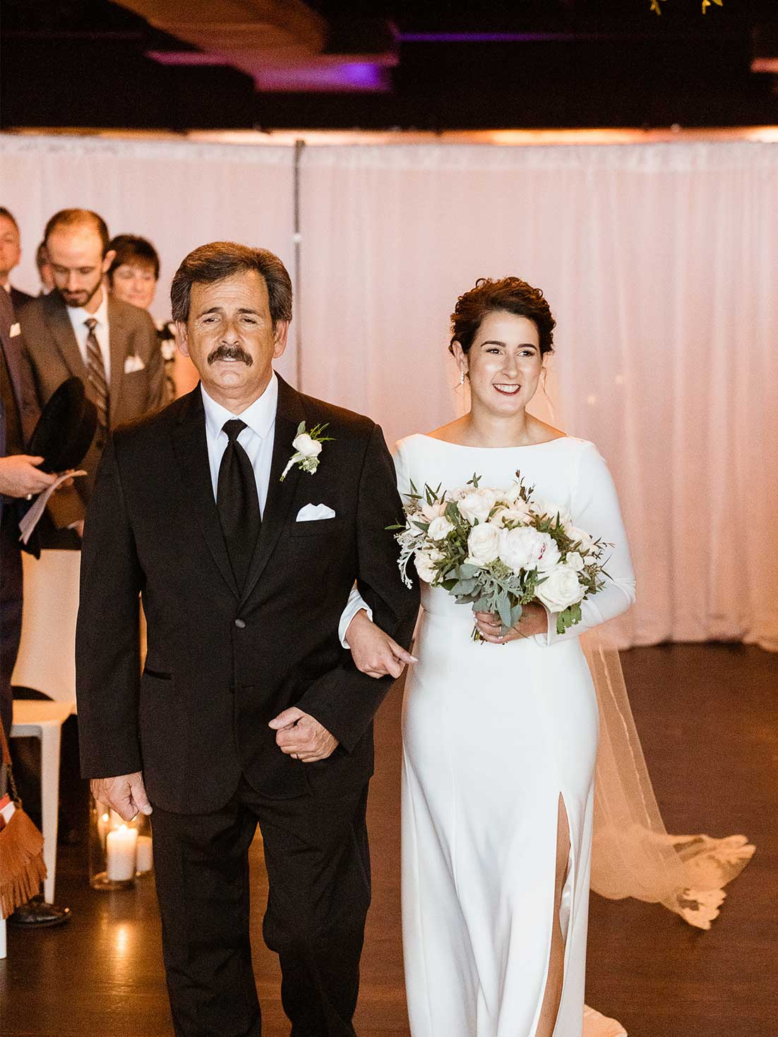 Smiling bride is escorted down the ceremony aisle by her father