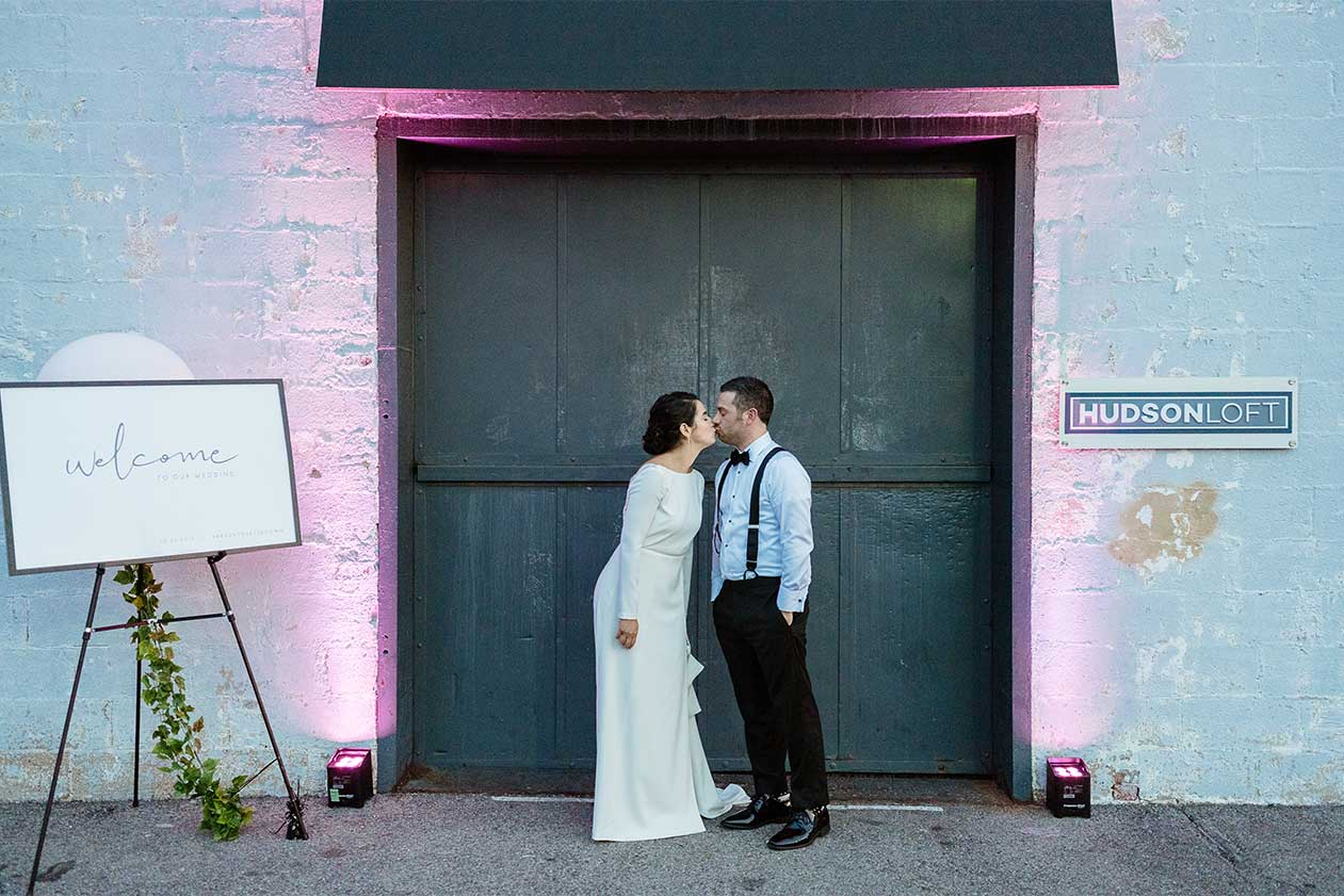 Wedding couple kissing in front of Hudson Loft's freight elevator, next to their welcome signage with ambient up lighting